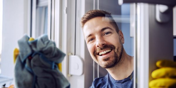 Portrait of young worthy smiling bearded man with rubber gloves on cleaning window at home.
