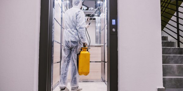 Sanitizing interior surfaces. Cleaning and Disinfection inside buildings, the coronavirus epidemic. Professional teams for disinfection efforts. Infection prevention and control of epidemic. Protective suit and mask.